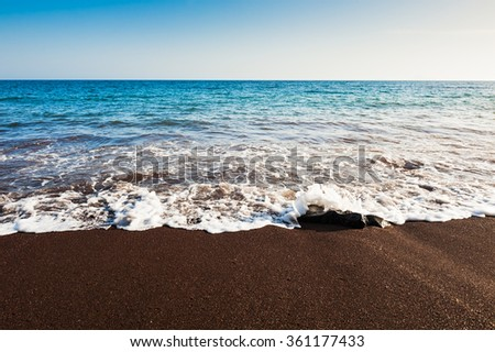 Beautiful beach with turquoise water and black volcanic sand. Red Beach, Santorini island, Greece - stock photo