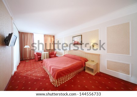 Beautiful bedroom with double bed with red linen, red armchairs and window. - stock photo
