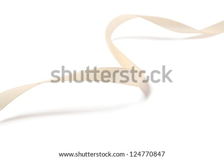 Beautiful beige ribbon with a bow. Isolated on a white background - stock photo