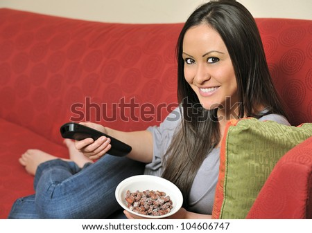 Beautiful bi-racial woman (Asian and Caucasian) resting on red couch holding a television remote control and a bowl of salted almonds - healthy snacking - stock photo