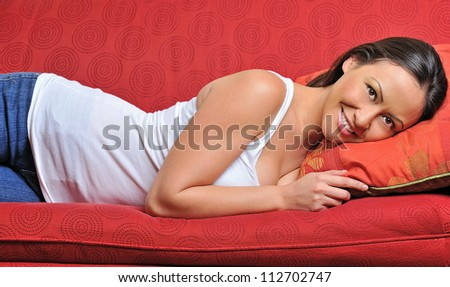 Beautiful bi-racial woman (Asian and Caucasian) resting on red couch in white tank top and blue jeans - smiling - stock photo