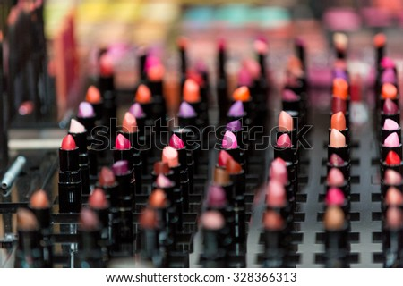 Beautiful big multicolor professional makeup set of many different colorful lipsticks in black plastic tubes in show case, horizontal picture - stock photo