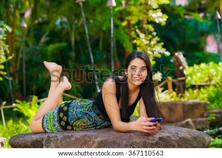 Beautiful biracial Asian Caucasian teen girl lying on rock in tropical setting looking at cellphone, palm trees in background - stock photo