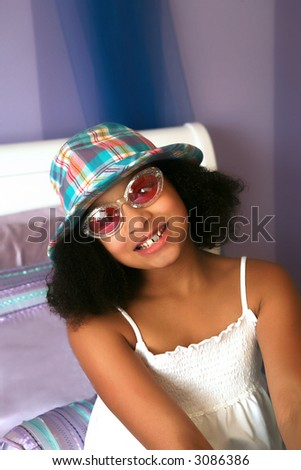 Beautiful biracial girl with hat and sunglasses - stock photo
