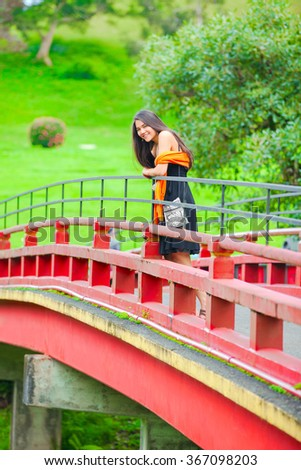 Beautiful biracial teen girl in black sundress standing alone on red Asian style bridge with green background - stock photo