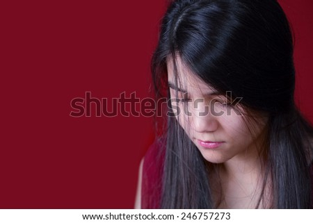 Beautiful, biracial teen girl looking down, depressed or sad, on red background - stock photo