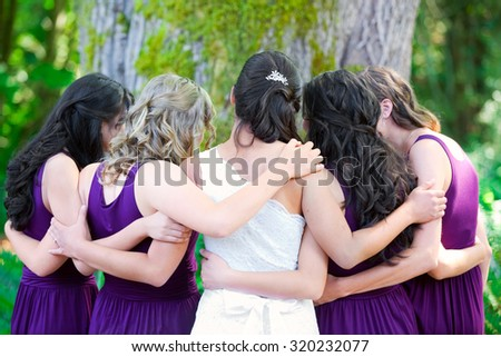 Beautiful biracial young bride  with her multiethnic group of bridesmaids in purple dresses, hugging in a huddle - stock photo