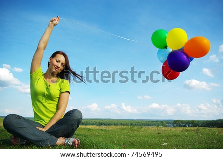 Beautiful birthday girl sitting with colorful baloons - stock photo
