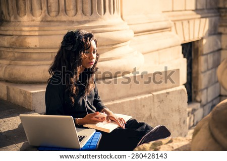 Beautiful black girl working with her laptop outside an old cathedral in London. - stock photo