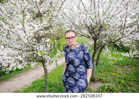 Beautiful black hair woman in glasses enjoying blooming tree , pretty woman relaxing outdoor. Happy young lady and spring green nature.  Gardens. - stock photo