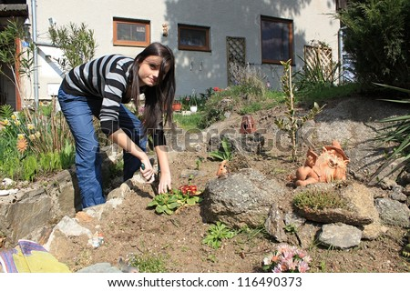 beautiful black-haired young girl working in the garden - stock photo