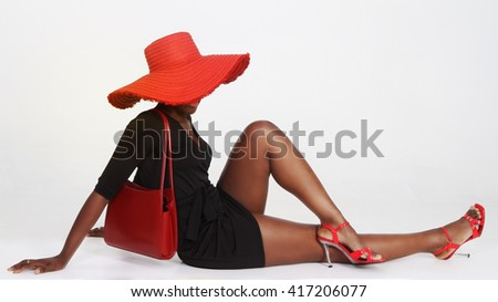 Beautiful black woman in a black dress and red accessories, red hat, red bag, red shoes, sits and shows her pretty legs, elegant photography made in studio on white background. - stock photo
