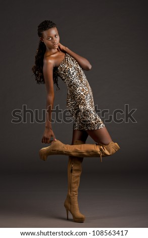 beautiful black woman in animal print dress leans back as she grabs onto the heel of her boot creating several lines with her body - stock photo