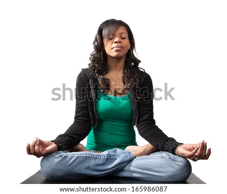 Beautiful black woman practicing Yoga in jeans and a tank top in the lotus position isolated on white. - stock photo