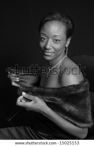 Beautiful black woman removing her fur stole - stock photo