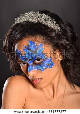 Beautiful black woman wit face-art. Studio shot on dark background. - stock photo