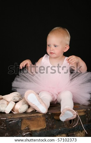 Beautiful blond baby wearing a ballet costume sitting on top of antique trunk - stock photo