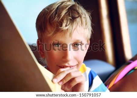 Beautiful blond boy in a colorful t-shirt reads the menu in a restaurant and smiles happily   - stock photo