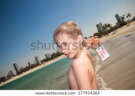 "Beautiful blond boy standing on a beach holding a bottle with a message ""need a break"". Stress and vacation concept.   - stock photo"