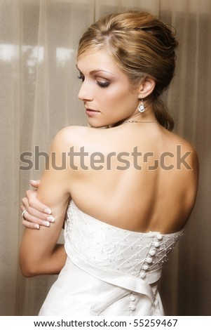 Beautiful Blond bride wearing diamond jewelery looking over her shoulder - stock photo