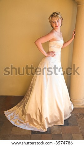 Beautiful blond bride with short hair in beige pearl dress leaning against a pillar - stock photo