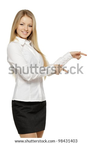 Beautiful blond business woman pointing at copy space over white background - stock photo
