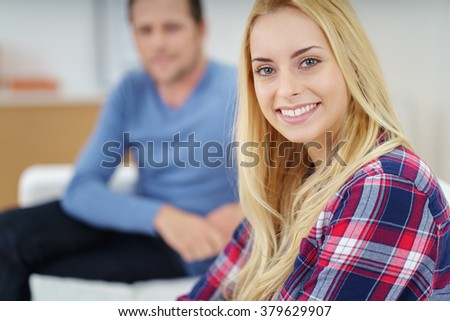 Beautiful blond Caucasian woman in flannel shirt sitting near man in blue shirt out of focus - stock photo