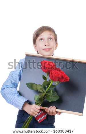 Beautiful blond child wearing formal shirt and a tie showing red roses and a blackboard (education concept)  - stock photo