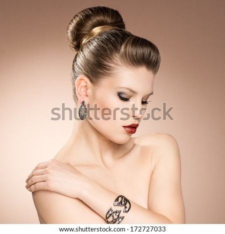 Beautiful blond fashion girl with evening hairdo and professional make-up wearing black jewelery. Portrait of young Caucasian pretty woman with red juicy lips.   - stock photo