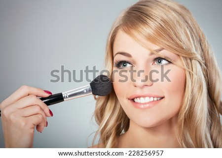 Beautiful blond fashion model applying blusher on cheeks - stock photo