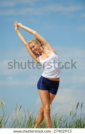 Beautiful blond female workout on the beach - stock photo