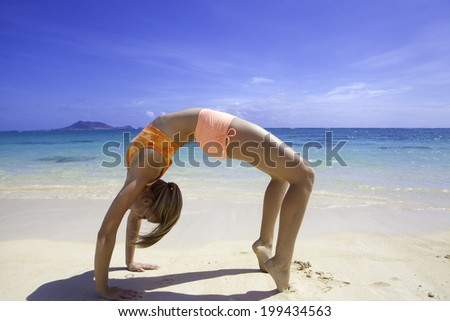 beautiful blond girl at the beach in hawaii doing yoga - stock photo