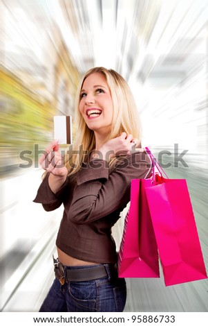 Beautiful blond girl buyer with credit card and shopping bags - stock photo