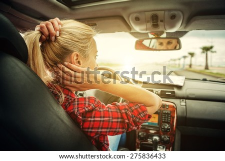 Beautiful blond girl comb her hair with a rear view mirror in car - stock photo