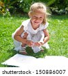 beautiful blond girl drawing a notebook on the grass - stock photo