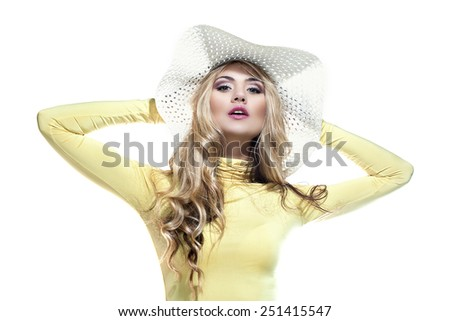 Beautiful blond girl in a hat enjoying the sun on the beach - stock photo