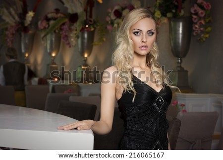 beautiful blond girl in black dress near a luxory bar , posing and looking in camera . she has hair do - stock photo