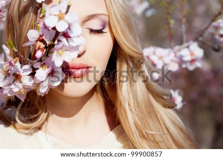 Beautiful blond girl in blossom garden - stock photo