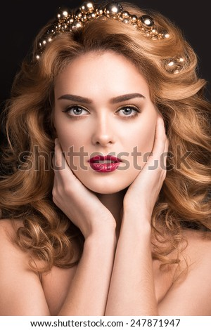 Beautiful blond girl in the image of a bride with a tiara in her hair. Picture taken in the studio on a black background. Beauty face. Wedding image. - stock photo