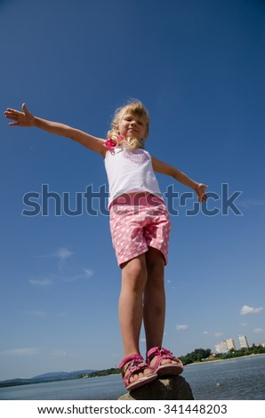 beautiful blond girl in the stone by the river with opened hands like flying - stock photo