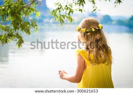 beautiful blond girl in yellow dress with flower headband by the river strand back view - stock photo