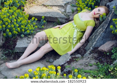 Beautiful blond girl lying among the rocks and spring flowers - stock photo