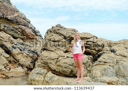 Beautiful blond girl meditate on the beach - stock photo