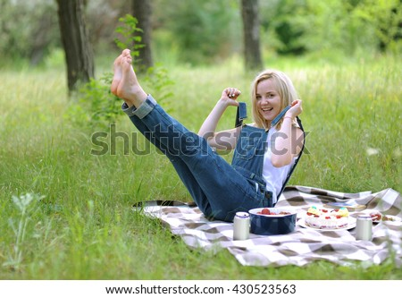 Beautiful blond girl on a picnic in the woods on a checkered mat. Young woman on a picnic in summer park. Funny cheerful girl in denim overalls in a pose in a pin up style. Girl fooling around - stock photo