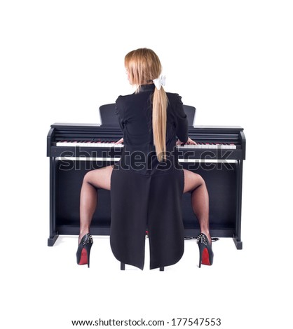 Beautiful blond girl playing piano. Isolated on a white background. Studio shot - stock photo