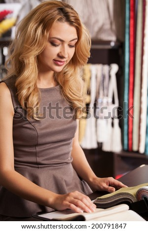 beautiful blond girl selecting color. attractive lady sitting in store and smiling - stock photo