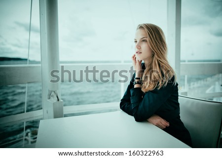 Beautiful blond girl sits in caffee at table - stock photo