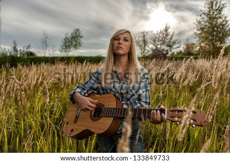 Beautiful blond girl with a guitar on a meadow - stock photo