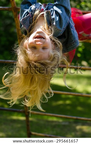beautiful blond girl with long hair playing in playground - stock photo