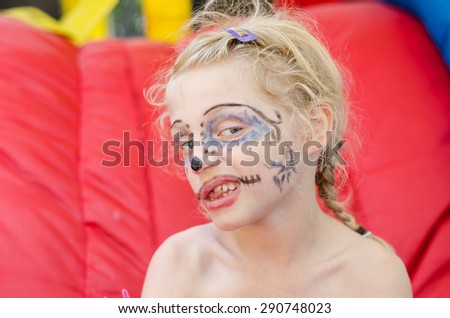 beautiful blond girl with scary facepainting - stock photo
